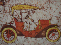 Antique car in Batik (yellow roof, tires and horn, red body and spokes, brown underside and batiked background on white)